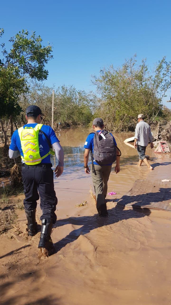 Voluntarios de CADENA cruzan una zona inundada.