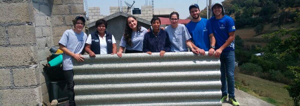 Voluntarios cargan un techo de TetraPak