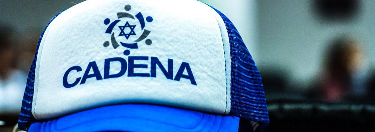 Una gorra azul y blanca, con el logotipo de CADENA al frente.