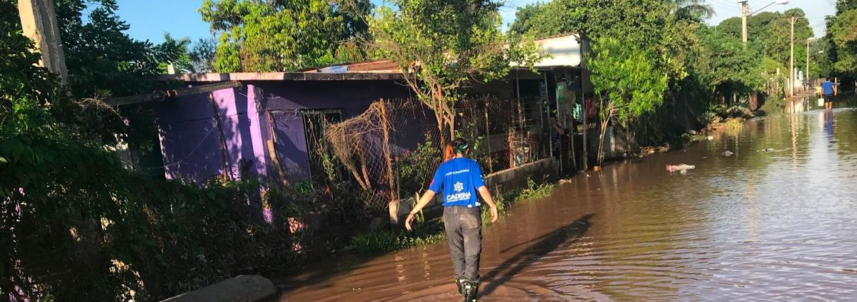 Un voluntario CADENA camina sobre la inundación en SInaloa