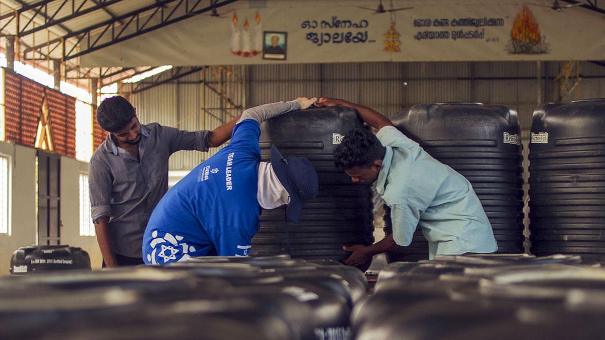 Un voluntario CADENA y un ciudadano Indio ayudan a cargar un tanque de agua en la misión a Kerala.