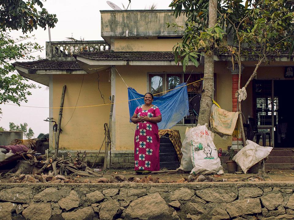 Mujer de Kerala, India sonríe frente a su puerta