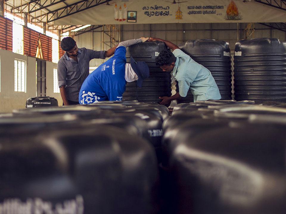 Un voluntario de CADENA baja con un voluntario de India un tanque de agua.