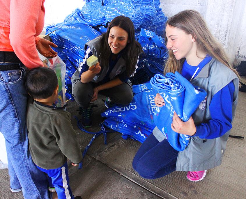 Dos jóvenes voluntarias de Juventud CADENA reparted cobijas a una madre con su hijo pequeño.