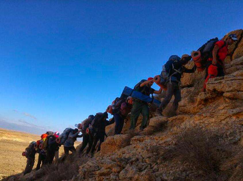 Participantes del curso de rescatista escalan una colina.