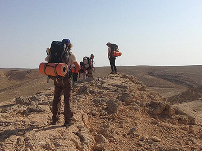 Participantes del curso de rescatista escalan terreno difícil como parte de su entrenamiento