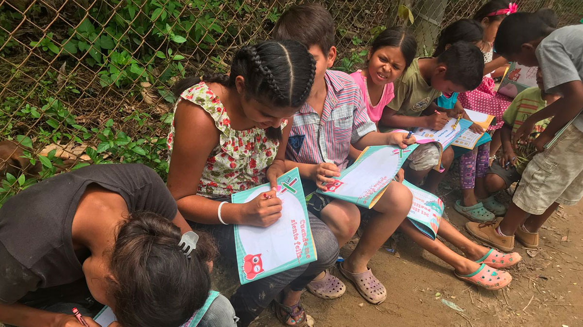 Children participate during a creative writing exercise during a CADENA mission.